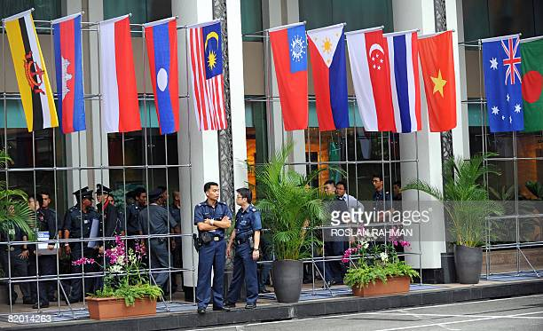 Two policemen stand under rows of flags from the Association of Southeast Asian Nations grouping the European Union China Russia and the US at the...