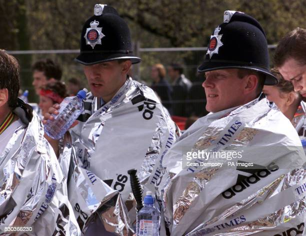 Two Policemen take a well earned rest after their run at the end of the Flora London Marathon 2000 in London Sunday 16 April 2000