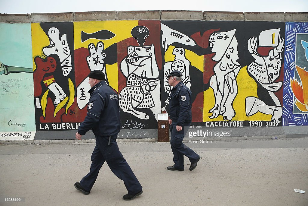 Two policemen walk past an already partially dismantled portion of the East Side Gallery, which is the longest still-standing portion of the former Berlin Wall, next to where a new hotel is scheduled to be built on February 28, 2013 in Berlin, Germany. According to media reports the developer in charge of the project plans to remove an approximately 25-meter long piece of the Wall and transfer it elsewhere in order to allow access to the construction site. Critics, including East Side Gallery mural artists and Spree River embankment development opponents, decry the move, citing the East Side Gallery's status as a protected landmark and a majortourist attraction.