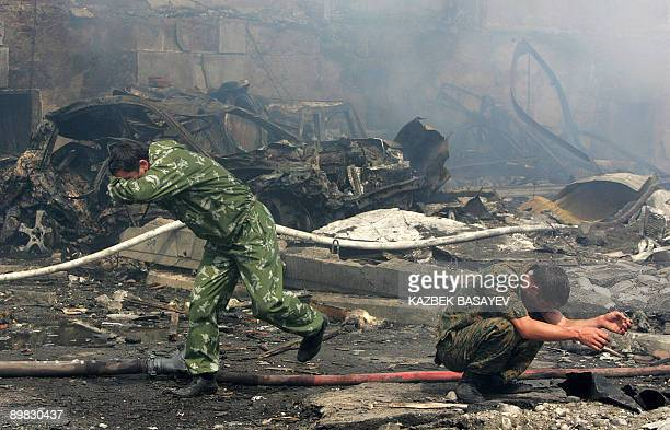 Two policemen work at the site of an explosion in a police compound in Nazran on August 17 2009 A truck packed with explosives rammed through the...