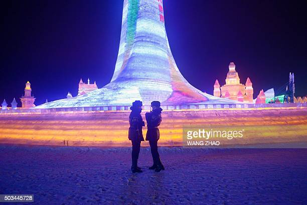 Two policewomen chat in front of ice sculptures at the China Ice and Snow World during the Harbin International Ice and Snow Festival in Harbin...