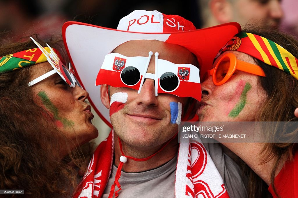Two Portugal supporters kiss a Poland supporter ahead of the Euro 2016 championship match between Poland and Portugal, in Marseille, southern France, on June 30, 2016. / AFP / JEAN