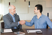 Two business partners shaking hands to each other after closing deal. Young entrepreneur grateful for help of senior legal adviser. Business meeting and partnership concept