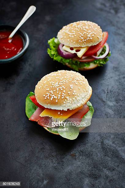 Two prepared burgers, mustard and ketchup on dark ground