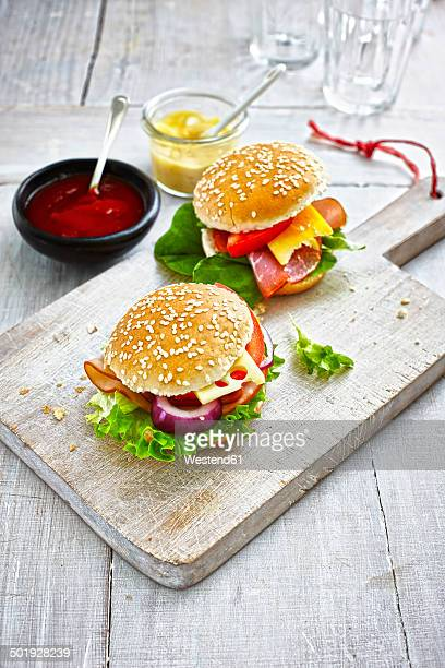 Two prepared burgers, mustard and ketchup on wooden ground