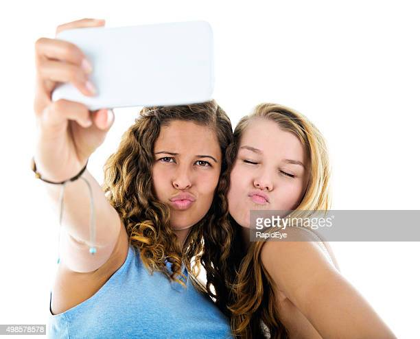 Two pretty girls take a selfie, pulling silly faces