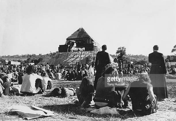 Two priests walking amonmg the crowds of festivalgoers pictured from behind looking toward the Pyramid stage at the Glastonbury Festival at Worthy...