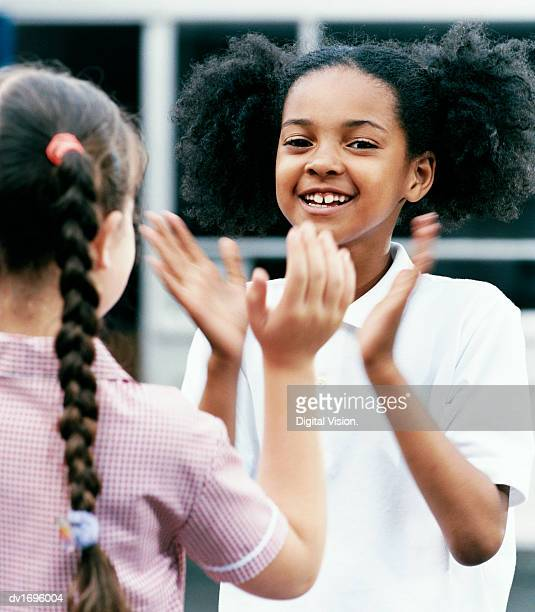 Two Primary School Girls Playing Patacake Face to Face in the Playground