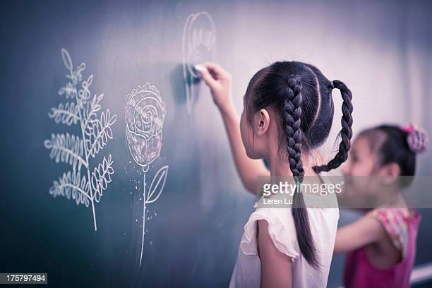 Two primary students drawing on blackboard