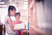 Two primary students reading in library