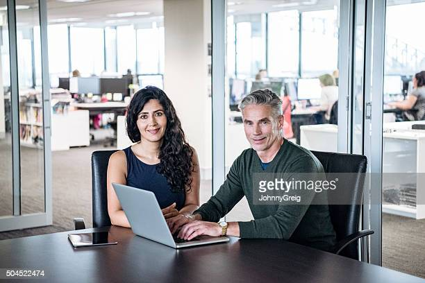 Two professional business people using laptop in office