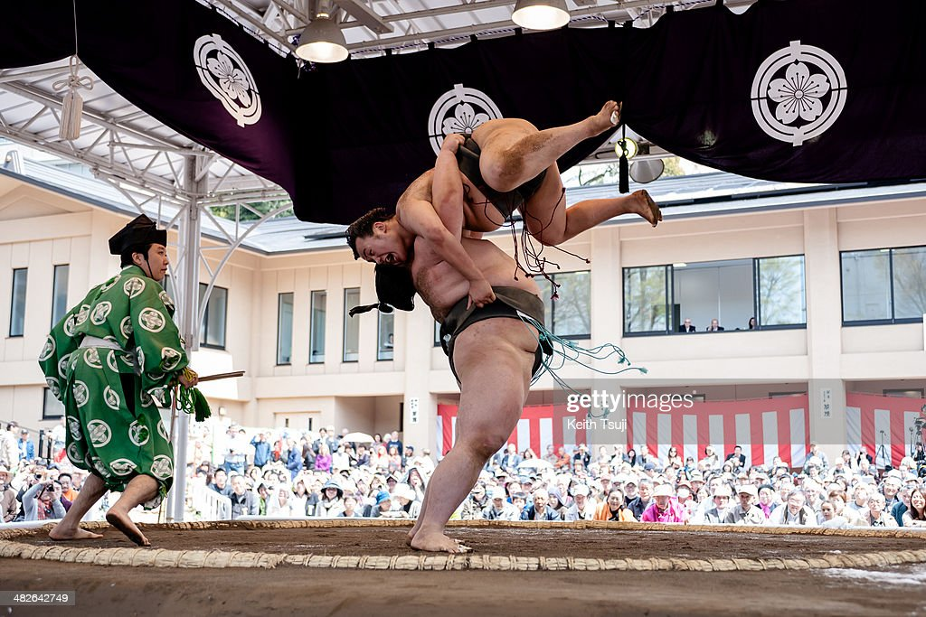 Two professional sumo wrestlers compete with each other during the Ceremonial Sumo Tournament or Honozumo at the Yasukuni Shrine on April 4, 2014 in Tokyo, Japan.