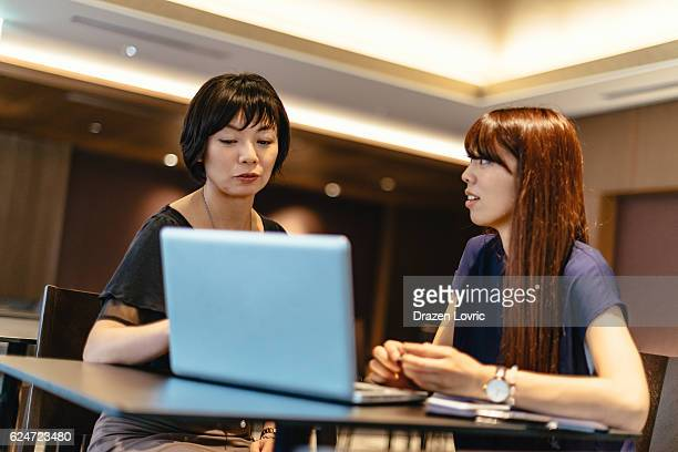 Two professional women in financial business in Japan working together