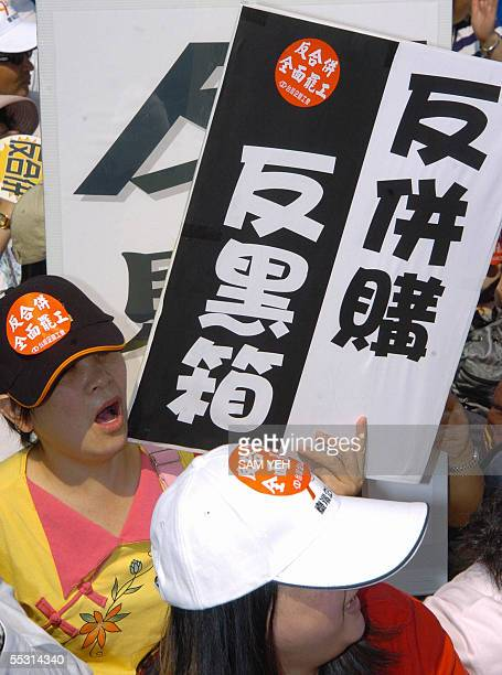 Two protesters display placards that read 'anti merger and undertable deal' during a demonstration outside the Taiwan Business Bank headquarter in...