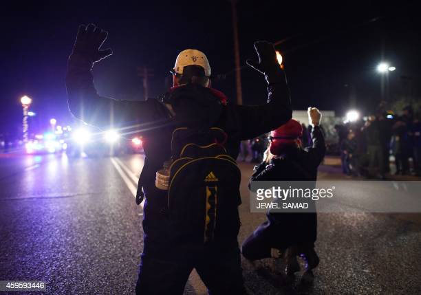Two protesters hold their hands up as they kneel on the street in front of a police car in Ferguson Missouri on November 25 2014 during a...
