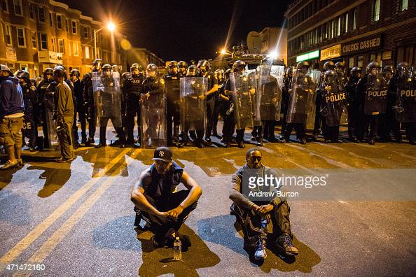 Two protesters sit on the ground in front of riot police minutes before a mandatory citywide curfew of 10 pm near the CVS pharmacy that was set on...