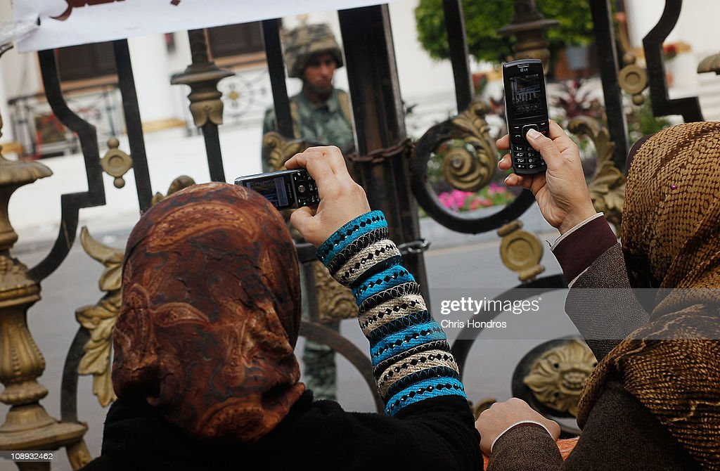 Two protesting women take pictures of an Egyptian Army soldier guarding the Egyptian Parliament building on February 9, 2011 in Cairo, Egypt. Thousands of Egyptians protested outside of the parliament building in downtown Cairo to demand the assembly's immediate dissolution following waves of anti-government protests in the nearby Tahrir Square.