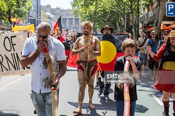 Two protestors playing the didgeridoo as man dressed in traditional Aboriginal attire plays the sticks during a rally organised to remember the First...