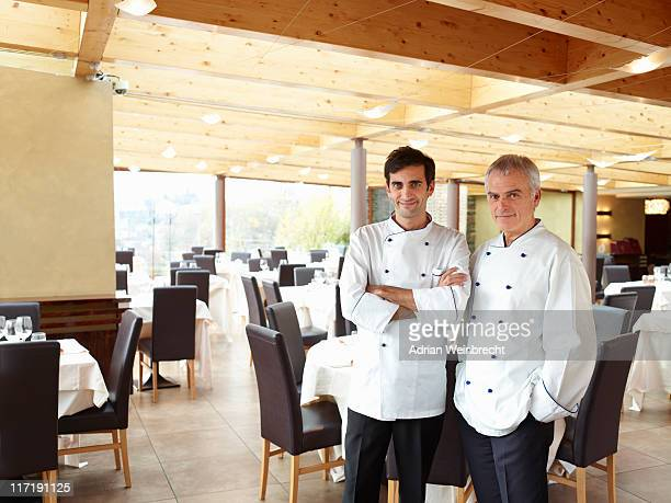 Two proud chefs in a large restaurant