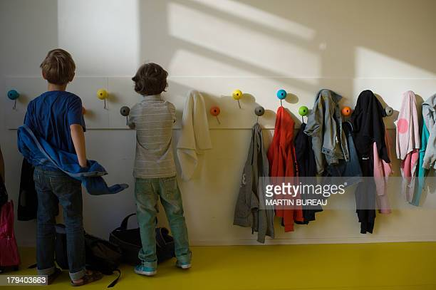 Two pupils take off their coats in the corridor of a primary school on September 3 2013 in Paris on the first day of school More than 12 million...
