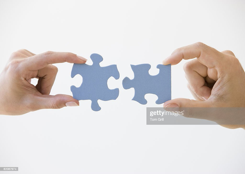 Two Puzzle Pieces Coming Together : Stock Photo