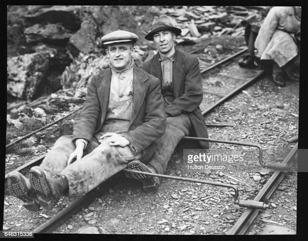 Two quarrymen from the Craig Ddu slate quarries near Blaenau Ffestiniog ride home on a track trolley called a 'cargwyllt' after work The trolleys...