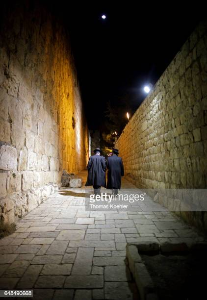 Two rabbis go through the historic city center of Jerusalem by night on February 08 2017 in Jerusalem Israel
