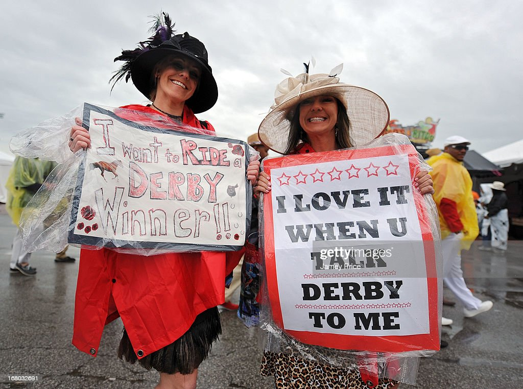 Two race fans hold up signs while standing in the infield, while it rains, prior to the 139th running of the Kentucky Derby at Churchill Downs on May 4, 2013 in Louisville, Kentucky.