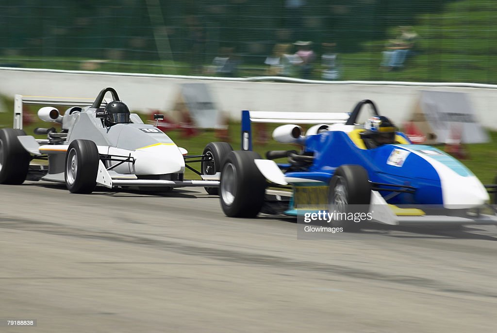 Two racecars racing on a motor racing track : Stock Photo