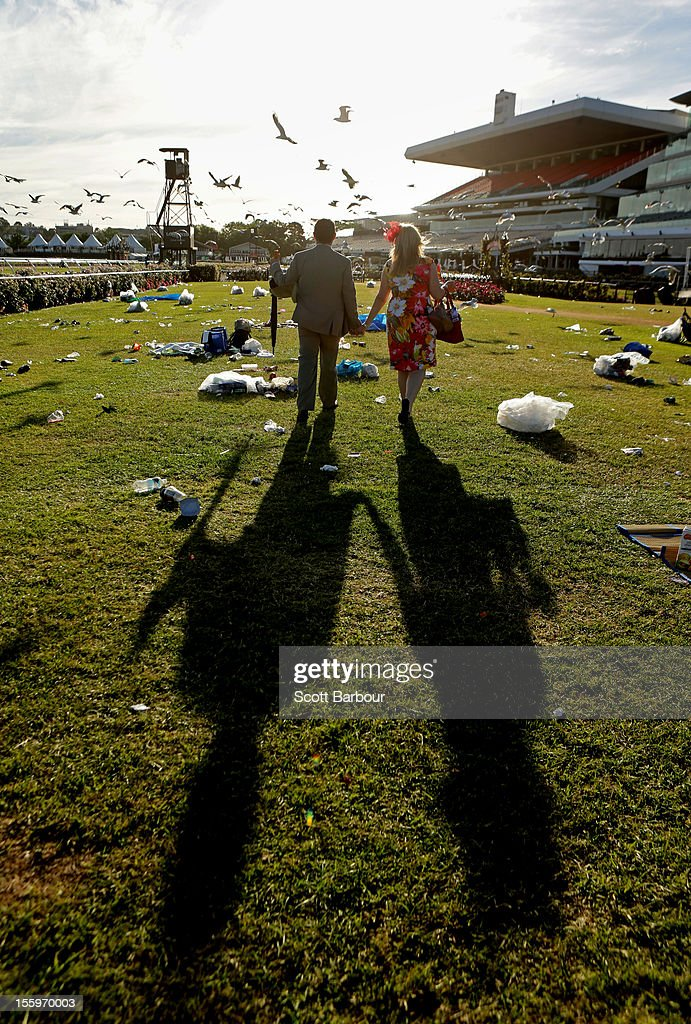 Two racegoers make their way home through the rubbish left behind after attending the 2012 Emirates Stakes Day at Flemington Racecourse on November 10, 2012 in Melbourne, Australia.