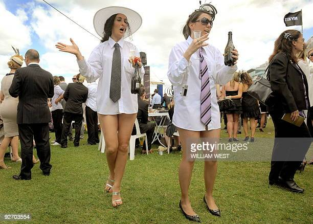 Two racegoers take a different approach to fashion before the running of the Melbourne Cup horse race on November 3 2009 A crowd over 100000 people...
