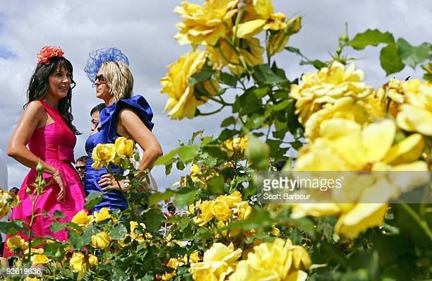 Two racegoers talk in front of spring flowers during the 2009 Melbourne Cup Day meeting at Flemington Racecourse on November 3 2009 in Melbourne...