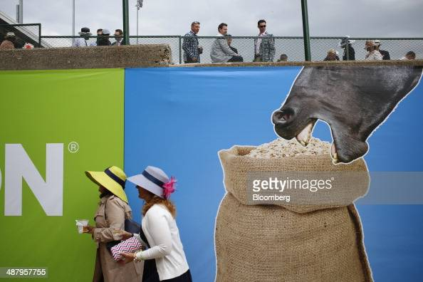 Two racegoers wearing Derby hats walk past a Groupon advertisement between horse races at Churchill Downs on the eve of the Kentucky Derby in...