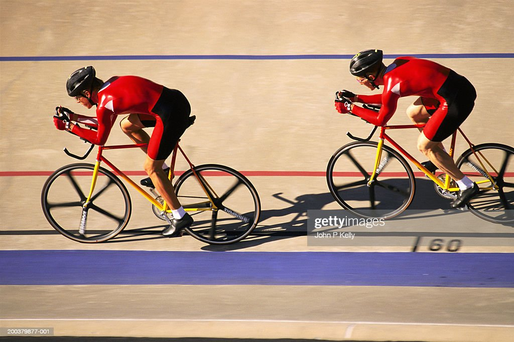 Two racing cyclists in velodrome, side view (blurred motion)