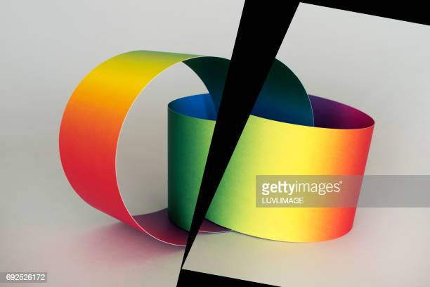 Two rainbow colored paper rings intertwined and separated.