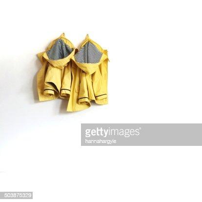 Two raincoats hanging on wall
