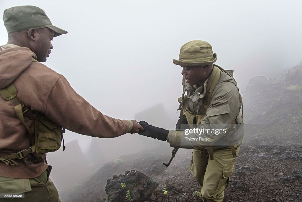 Two rangers in the morning mist exchange a communication device on the top of Mount Nyiragongo The Nyiragongo is an active stratovolcano with an...