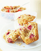 Two rasberry muffins on plate, by bowl of cereal (focus on muffins)