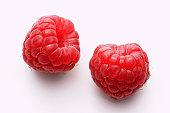 Two raspberries on white background