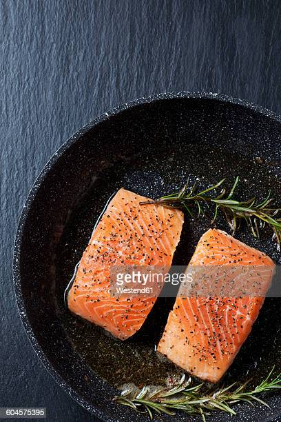 Two raw salmon fillets in a frying pan on slate