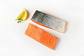 Two raw salmon fillets and lemon on white background