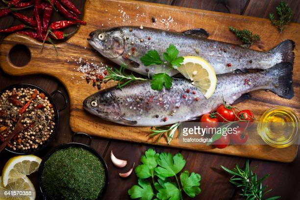 Two raw trout on dark slate background