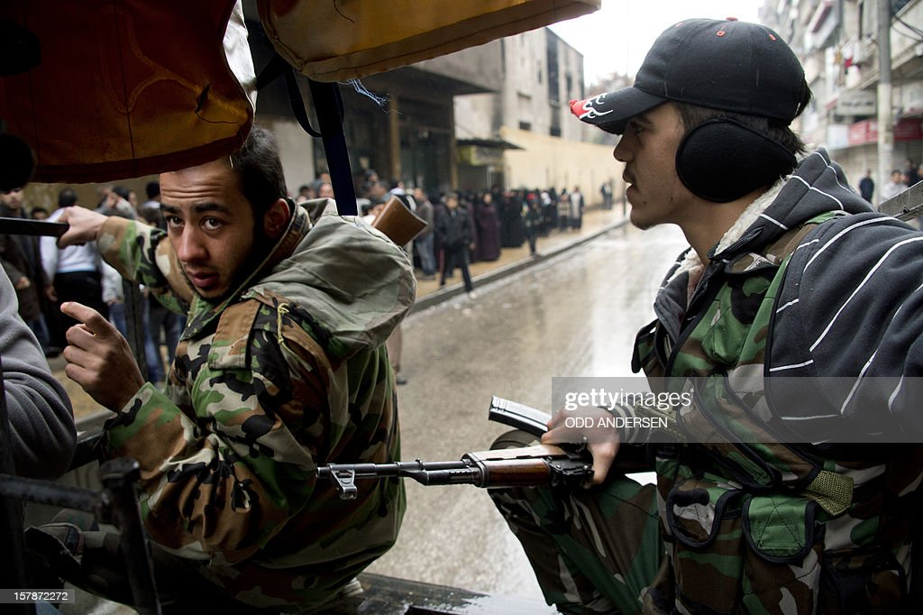 Two rebel fighters crouch on the back of their machine gun mounted pick up truck as they approach an exposed intersection in the Aleppo neighbourhood of Bustan al-Qasr on December 7, 2012. Syrian opposition groups had agreed in Doha last month to sink their differences and form a single body in the hope of getting direct aid, including crucial anti-aircraft weapons, to combat President Assad.