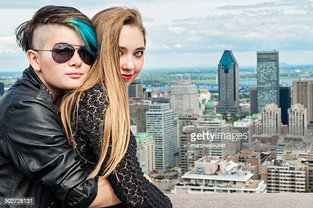 Two rebel teenagers hugging in front of Montreal cityscape.