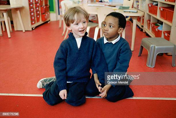 Two Reception Year pupils at Millfields Community School who are good friends listen to their teacher during their morning 'carpet time' This is a...