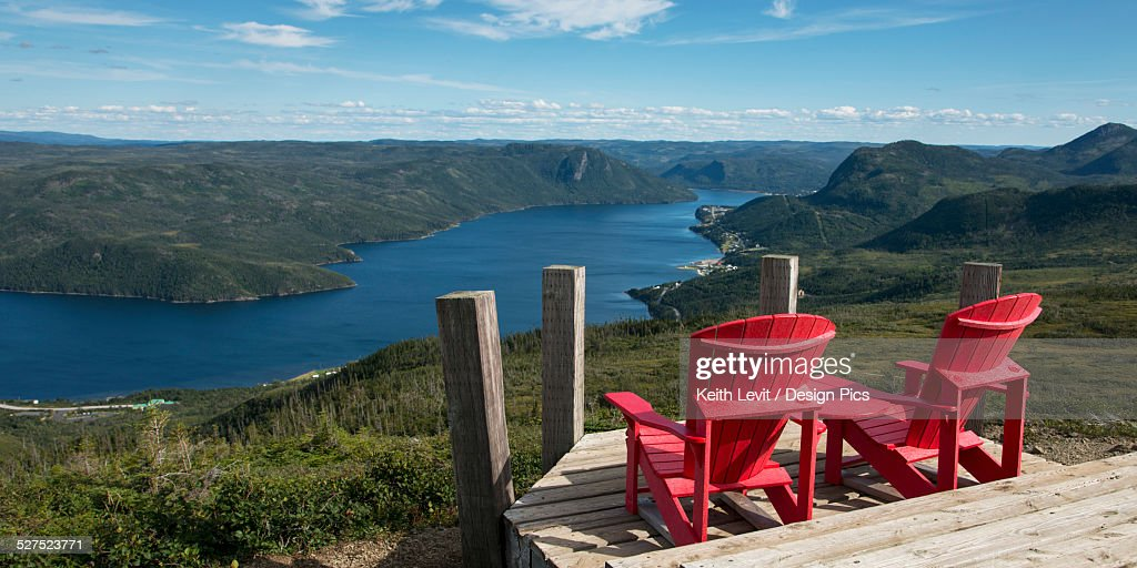 Two red adirondack chairs on a wooden observation deck overlooking Bonne Bay
