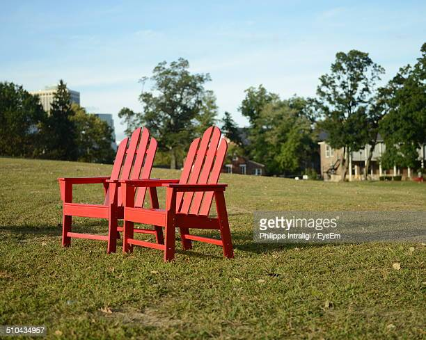 Two red Adirondack chairs on grassland against trees