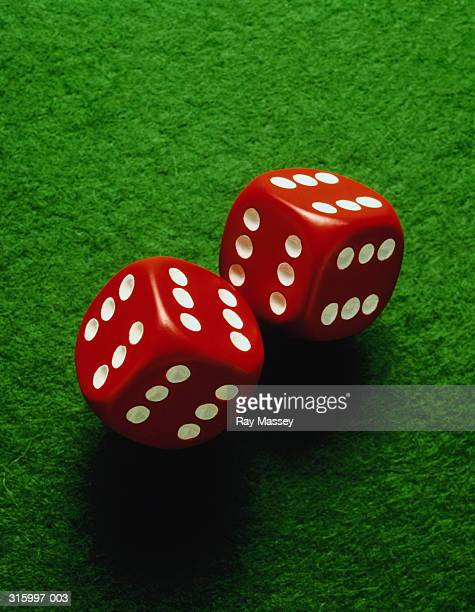 Two red and white dice on green felt,close-up