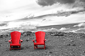 An image of two red chairs isolated on the side of a mountain.