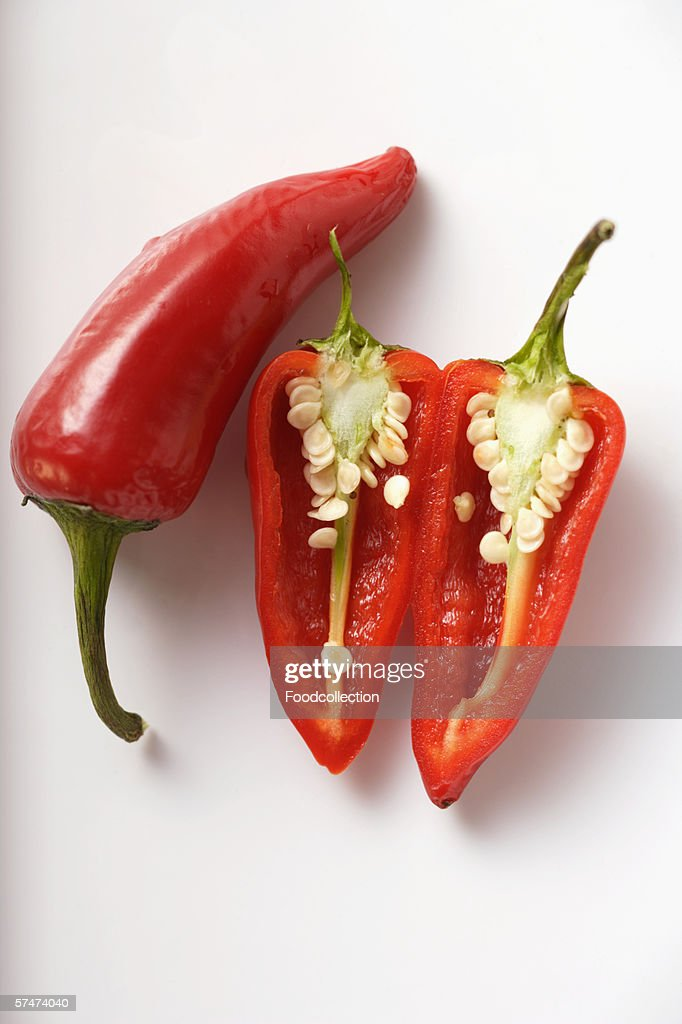 Two red chili peppers, one halved